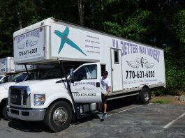 A Better Way Movers Office Manager John Kidney with one of the signature moving trucks at the company's Peachtree City location on Dividend Drive. Photo/Ben Nelms.