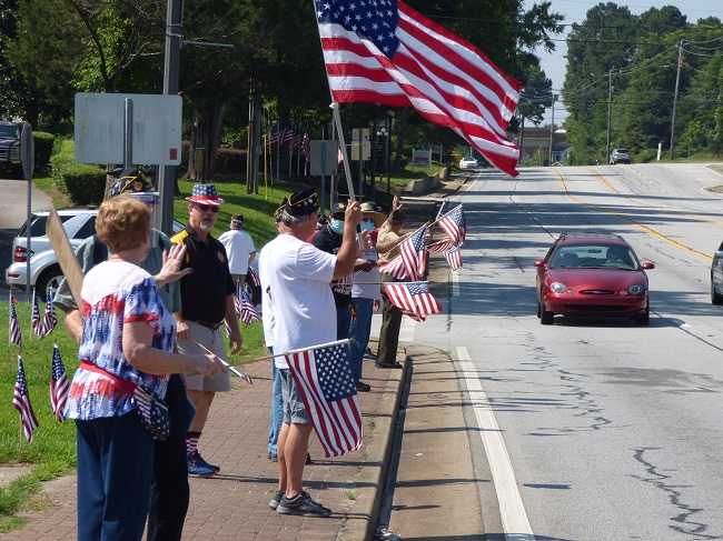 Patriotism was alive and well in Fayetteville on July 4, as members of Fayette County American Legion Post 105 lined South Glynn Street in front of the Log Cabin, waving flags and being recognized by the many motorists honking their horns in support. Photo/Ben Nelms.