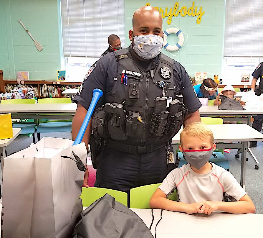<b>Fayetteville police officers representing their department's CARE unit presented first grader Caleb Eden with a baseball bat and related equipment for extraordinarily demonstrating the school's expectations of a Cleveland Crocodile.</b>