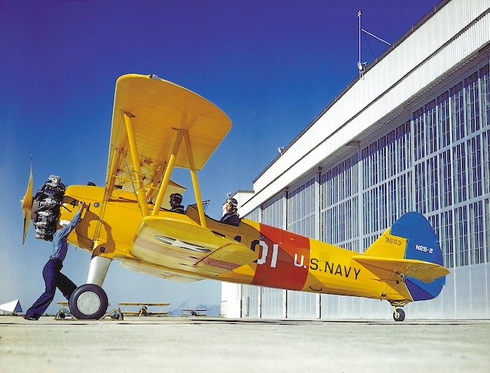 A U.S. sailor cranking the engine of a Stearman N2S-2 Kaydet (BuNo 3553) at the Naval Air Station Corpus Christi, Texas (USA), in 1943.