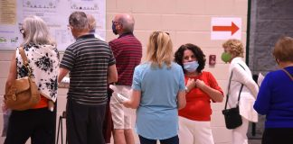 Peachtree City Mayor Vanessa Fleisch (in red facing camera) hears from a resident during the LCI Open House Oct. 22 at Kedron Fieldhouse. Photo/Cal Beverly.