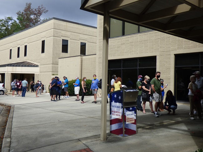 <b>Voters in line at the Peachtree City Library for the first day of early voting had the line extended up Willowbend Road and into the City Hall parking lot. Photo/Ben Nelms.</b>