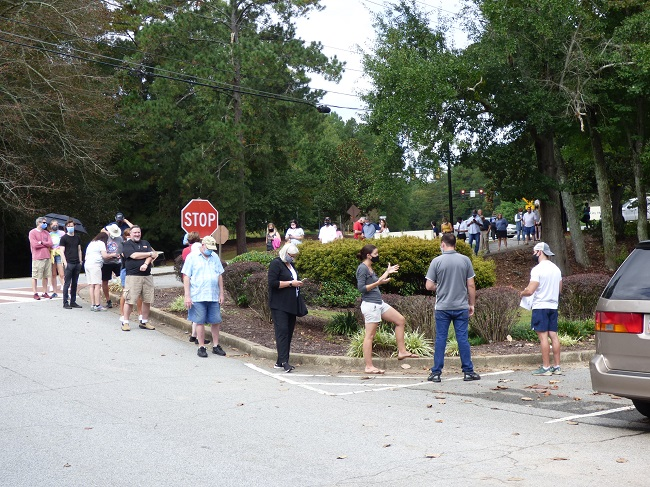 <b>Voting lines for the first day of early voting on Oct. 12 at the Peachtree City Library stretched into the parking lot and onto Willowbend Road. Photo/Ben Nelms.</b>