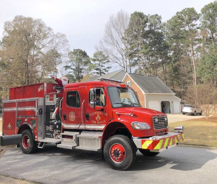 The jolly elf in the red suit was conveyed through Peachtree City neighborhoods Sunday courtesy of the Peachtree City Fire Department. His reindeer were unavailable for comment on the antique mode of transportation. Photo/Joyce Beverly.