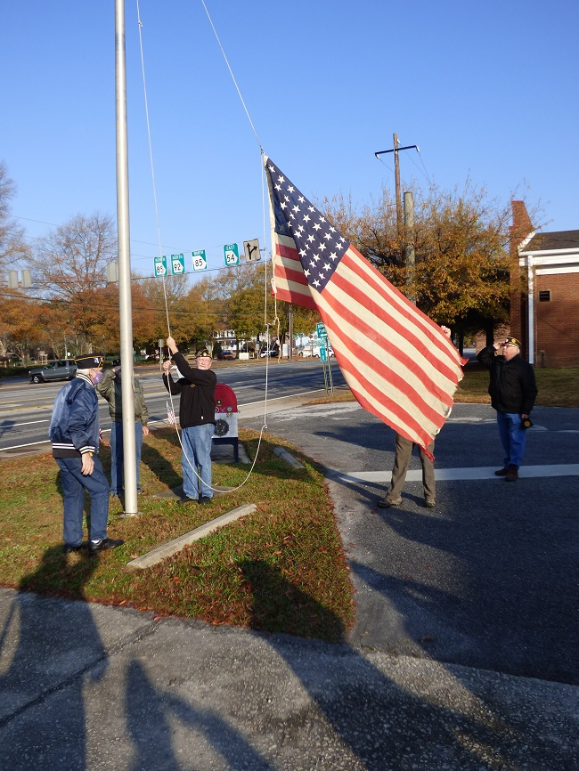 Members of American Legion Post 105 in Fayetteville on Dec. 7, Pearl Harbor Remembrance Day, raised a flag that flew over a military base in Malaysia during World War II. Photo/Ben Nelms.