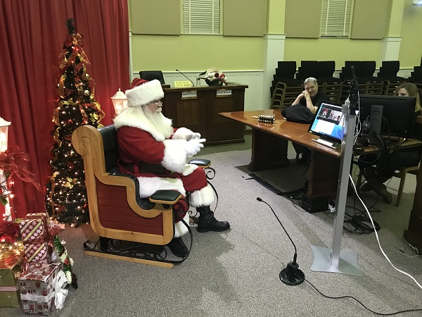 Santa stopped in at Fayetteville City Hall on Dec. 8 for a virtual visit with kids who wanted to make sure he knew all about their Christmas wishes. Sitting at the right were city IT staff Kelvin Joiner and Jessica Smith, who arranged the virtual visits. Photo/Ben Nelms.