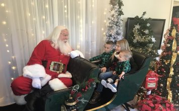 Fayetteville residents Parker Bryan, 5, (at left), Ali Bryan, 9, and J.T. Bryan, 2, were at Trilith in Fayetteville on Dec. 5 to spend time with Santa. Photo/Ben Nelms.