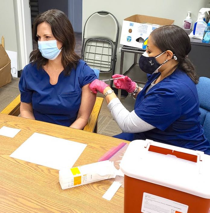 Rising Starr Middle school nurse Tiffany Blair receives the Moderna Covid-19 vaccination from a nurse at the Fayette County Health Department. Photo/Fayette County School System.