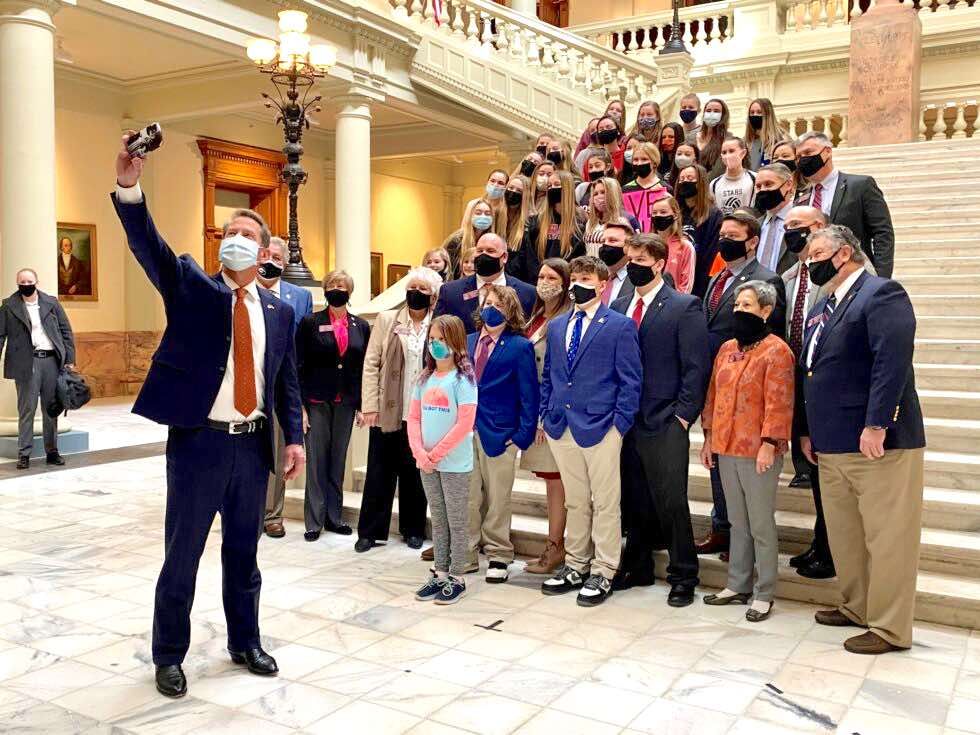 <b>Gov. Brian Kemp (left) takes a selfie with student athletes after a news conference to support legislation banning transgender participation in Georgia girls' sports on Feb. 4, 2021. Photo/Beau Evans of Capitol Beat News Service.</b>