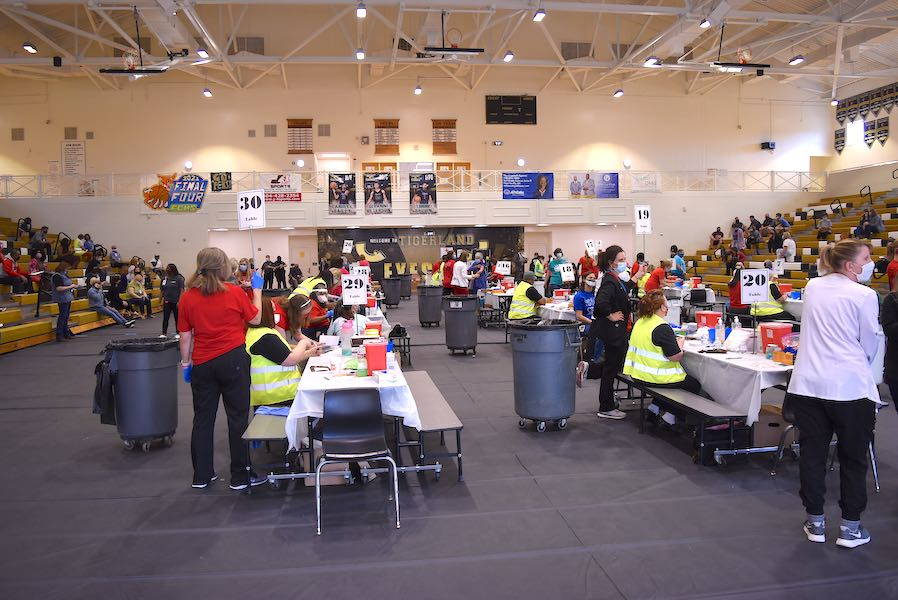<b>The gym floor housed 30 tables staffed by two school nurses each and other helpers to prepare school workers for the Covid-19 injections. Photo/Cal Beverly.</b>