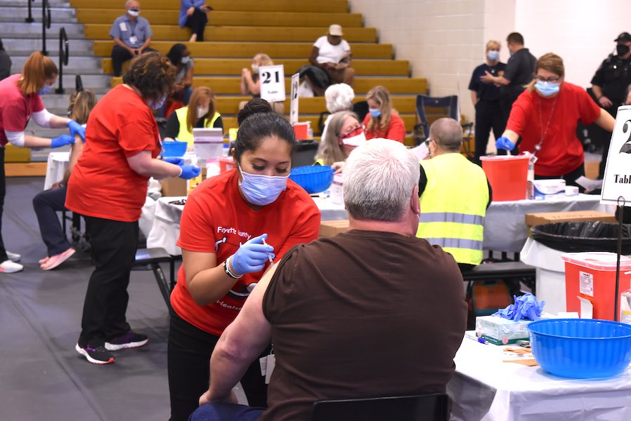 Fayette County School System nurses (in red pullovers) vaccinate system employees at a mass Covid-19 immunization event March 11 at the Fayette County High School Gymnasium. Photo/Cal Beverly.