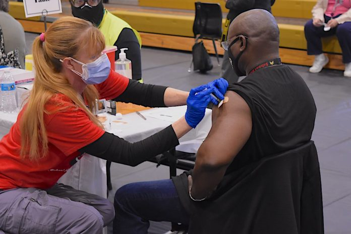 A Fayette County School System nurse injects an employee with the first dose of the Covid-19 vaccine at one of 30 stations on the floor of Fayette County High School Gymnasium March 11. Photo/Cal Beverly.