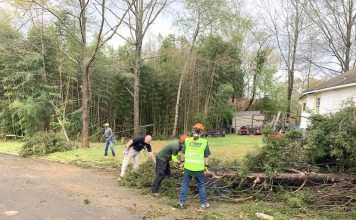 Members of the all-volunteer CERT team from the Peachtree City Police Department help clean up at one tornado-damaged home.