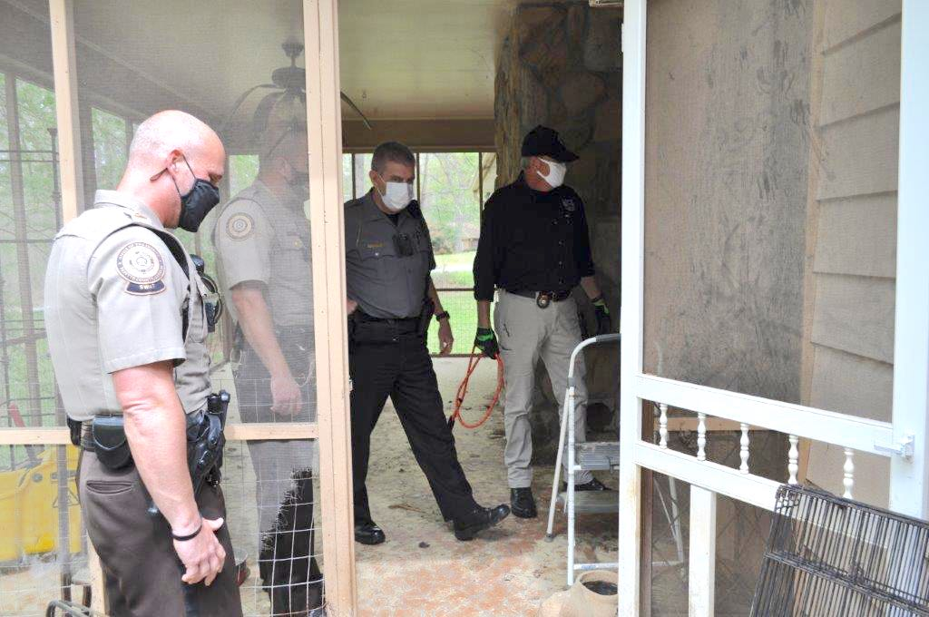 <b>Inside the animal-filled residence are (L-R), Jerry Collins, director of the Fayette County Animal Shelter (in black shirt), Chief Harold Myers of the Fayette County Marshals office and two deputies from the Fayette County Sheriff's Office. Photo/Submitted.</b>
