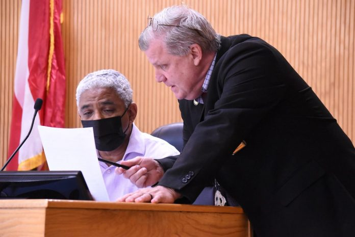 Fayette County Commissioner Charles Rousseau (L) and County Administrator Steve Rapson discuss agenda item before the regular meeting May 13. Photo/Cal Beverly.