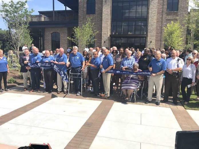 The Fayetteville City Council and City Manager Ray Gibson, all in blue shirts, cut the ribbon July 14 signifying the grand opening of the new Fayetteville City Hall on West Stonewall Avenue. They were joined for the event by a large group of Fayetteville staff and citizens, and elected officials from throughout Fayette County. Photo/Ben Nelms.