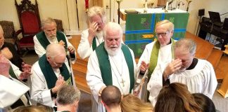 Bishop David Epps (center) and church members in prayer. Photo/submitted.
