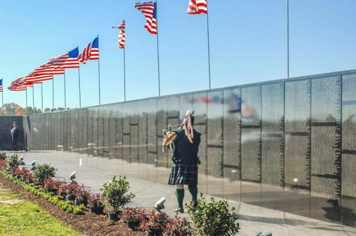 A Vietnam veteran plays the bagpipes at the Dignity Memorial Vietnam Wall. The exhibit crisscrosses the country each year, allowing millions of visitors to see and touch the black, mirror-like surface inscribed with the names of more than 58,000 Americans who died or are missing in Vietnam. The wall honors all U.S. veterans and is dedicated to Vietnam veterans. Photo/U.S. Navy .